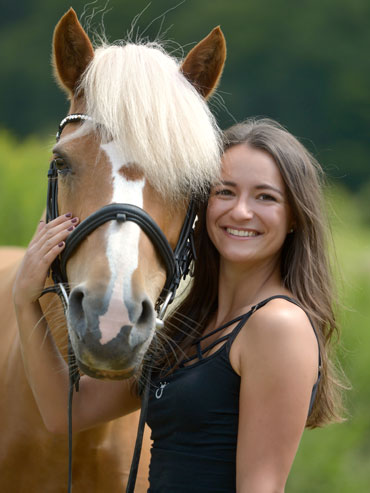 Teammitglied Julia posiert mit ihrem Pony Inka für ein Portraitfoto