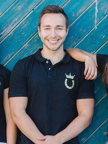 Robin posiert mit Royal Horsemen Poloshirt für Portraitbild